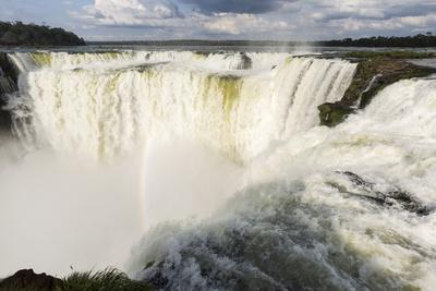 The headwater of Iguazu Falls with a rainbow from the Argentinian