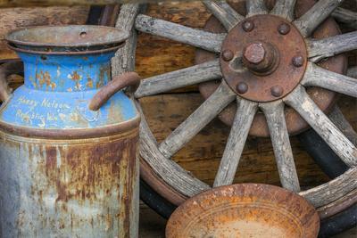USA, Alaska. Antique milk can, wagon wheel and gold pan.