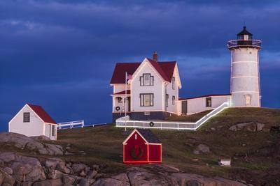 USA, Maine, York Beach, Nubble Light Lighthouse with Christmas decorations at dusk