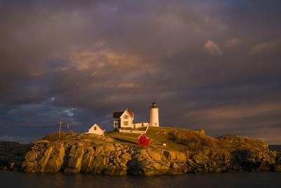 USA, Maine, York Beach, Nubble Light Lighthouse with Christmas decorations, sunset
