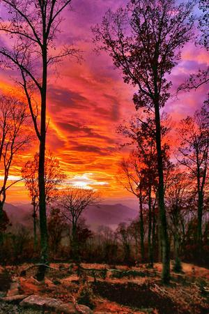 A mountainous area is filled with color at sunset.