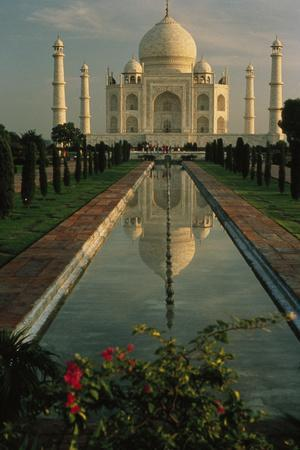 The Taj Mahal with a reflection of the tomb on  the surface of a pool.