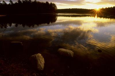 Clouds reflect in the Walden Pond at sunrise.