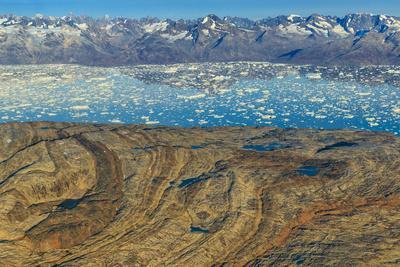 Aerial of folded metamorphic rocks and Icebergs in Sermilik Fjord.