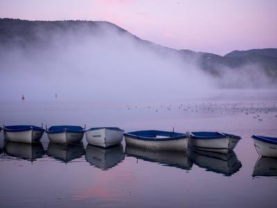 Fog rises from the water's surface at sunrise.