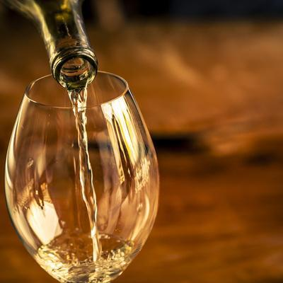 USA, Washington State, Seattle. White wine pouring into glass in a Seattle winery.