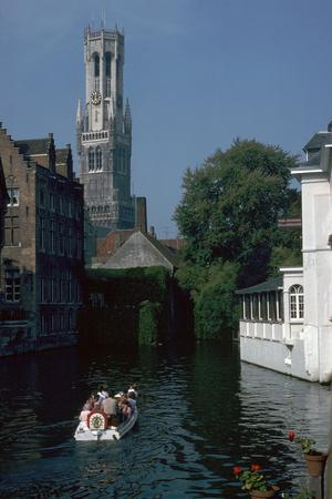 Canal, old houses, and the Belfrey of the Tour Des Halles in Bruges