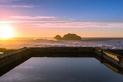 Sunset at Sutro Baths with water reflection in San Francisco with Pacific Ocean waves breaking