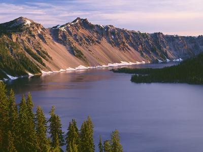 Oregon. Crater Lake NP, sunrise on west rim of Crater Lake with The Watchman and Hillman Peak