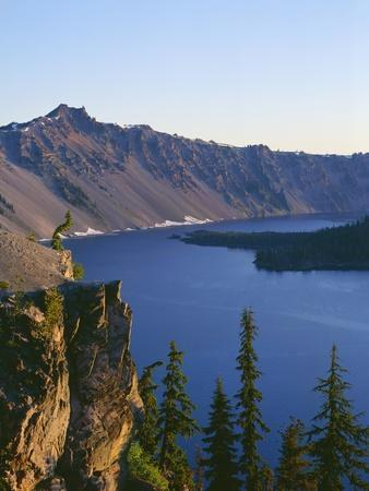 OR, Crater Lake NP. Sunrise on west rim of Crater Lake with Hillman Peak overlooking Wizard Island.