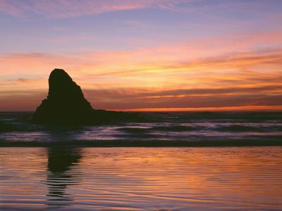 USA, Oregon. Ecola State Park, sunset over sea stack at Indian Beach.
