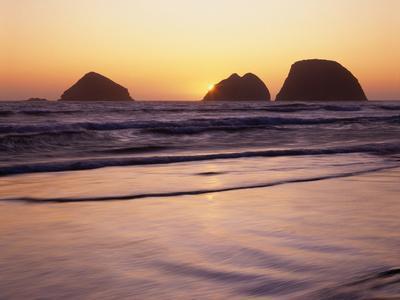 USA, Oregon, Oceanside Beach State Wayside. Sunset over Three Arch Rocks.