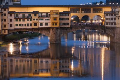 Italy, Tuscany, Florence, Ponte Vecchio reflected in Arno River at dusk.