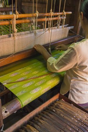 Myanmar. Shan State. Inle Lake. Woman weaving silk at a wooden loom.